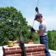 трубочист чистит дымоход на крыше