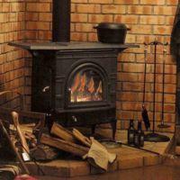 дрова и топор перед чугунным камином в доме фото