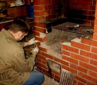 печник делает ремонт печи сидя на корточках фото