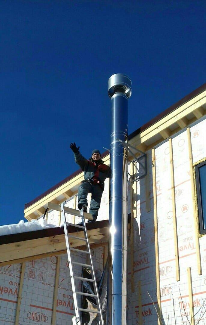 установка стального дымохода мужчина на крыше