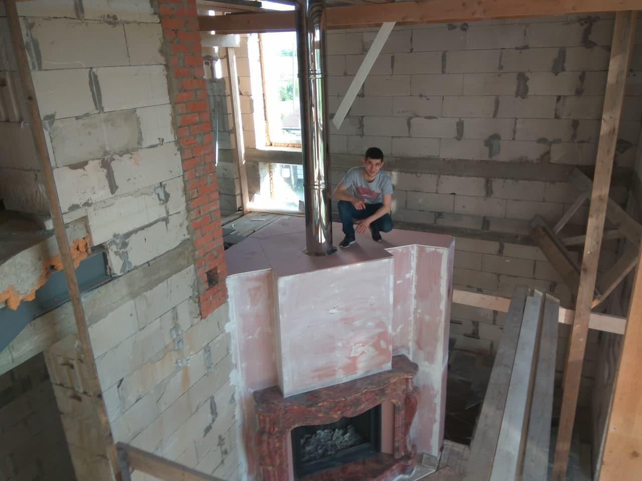 мужчина занимается монтажом камина в большом загородном доме