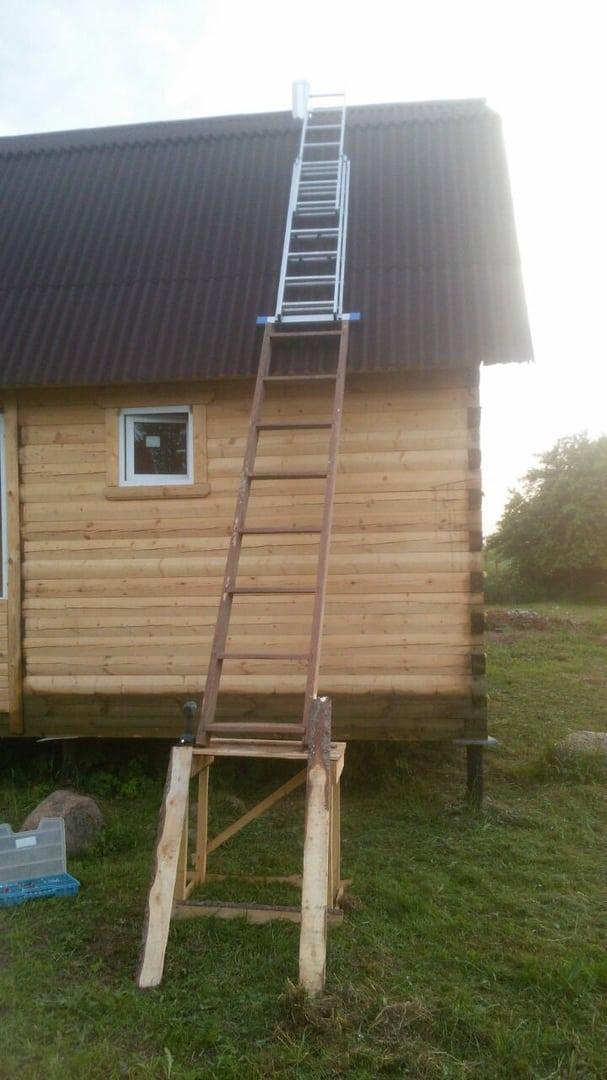 процесс установки стального дымохода на крышу загородного дома